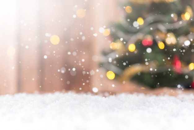 Snow background with blur bokeh of decorated chritmas tree