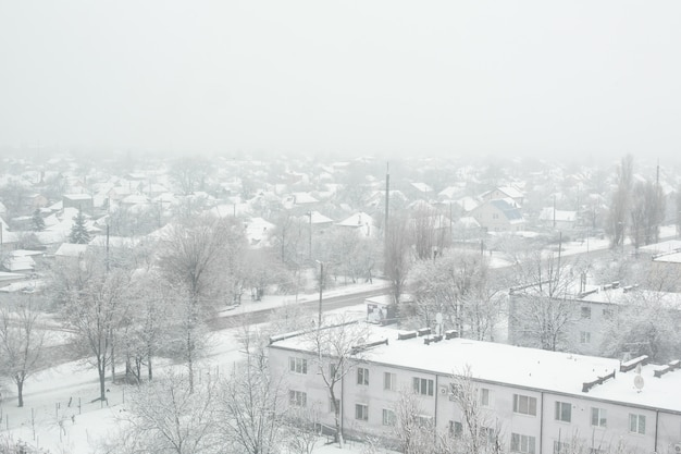 Snow blizzard in a small town, everything is covered with white snow.