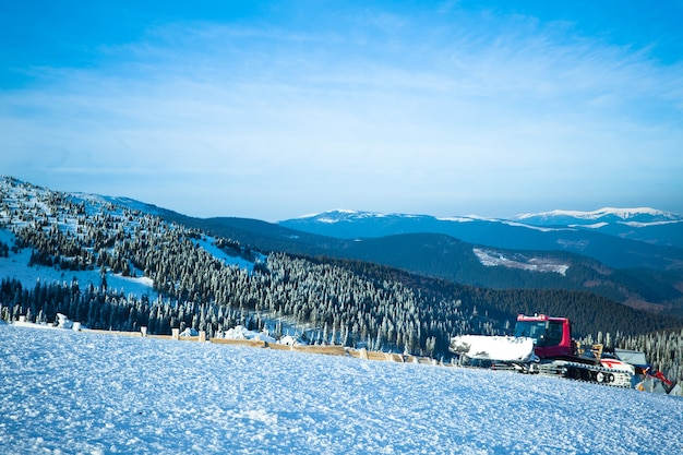 Snow blower machine working in ski resort with forest and mountains at background on sunny clear winter day with blue sky