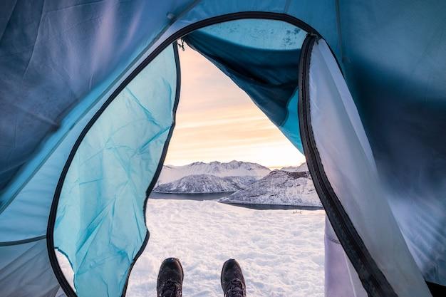 日の出の景色の雪の尾根とテントキャンプの入り口の中でリラックスしたスノーブーツ