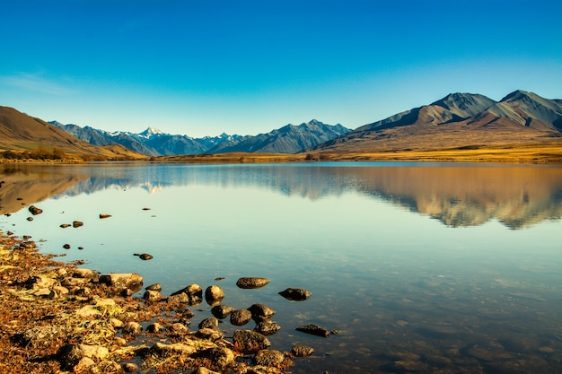 The snow capped mountain peaks of southern alps reflected in calm still water on lake clearwater, ashburton lakes high country