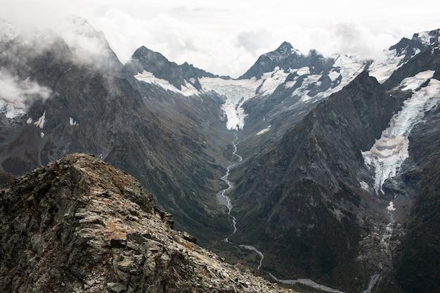 雲の中の雪をかぶった山脈。渓流のある谷。コーカサス、ロシア