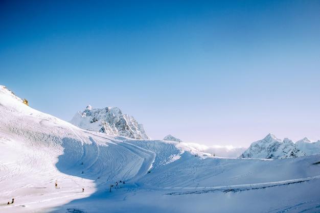 겨울에는 맑은 날에 눈 덮인 산. 스키어와 스노우 보더를 추적합니다. 동계 스포츠의 개념