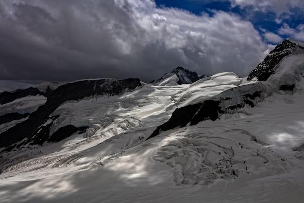 ニンバス雲の下の雪をかぶった山々