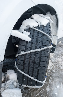 Snow chain puts on a wheel of a car
