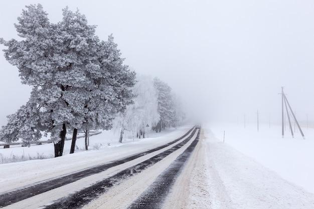 Заснеженная асфальтовая дорога через поля страны в тумане после метели.