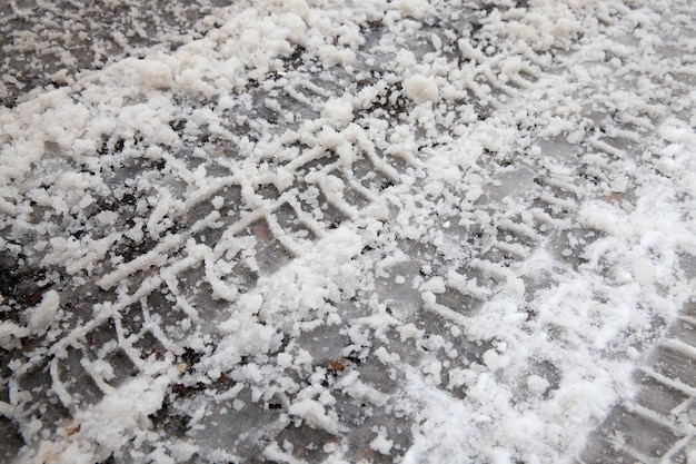 Snow covered asphalt, on the surface there are traces of passing cars, photo close up
