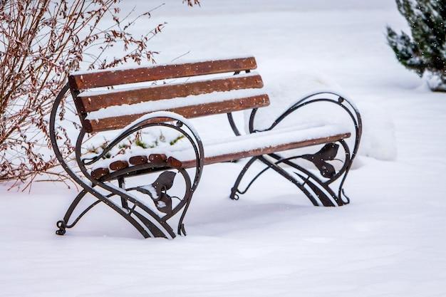 都市公園の雪に覆われたベンチ。最初の雪_