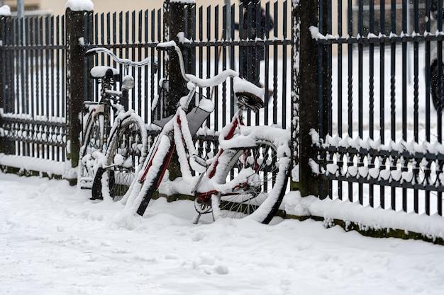 눈 덮인 자전거는 겨울 도시의 보도에 있는 울타리에 주차되고 잠겨 있습니다.