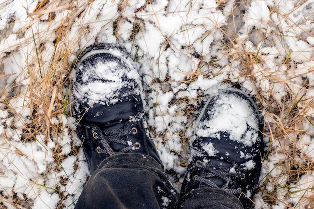 ウィンターパーク、上面図を歩いている間、彼の足で男の雪に覆われた黒いブーツ。雪の中で黒いブーツの男