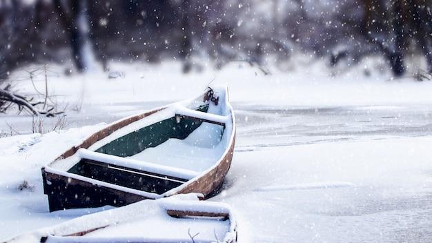 Заснеженная лодка на реке зимой во время снегопада