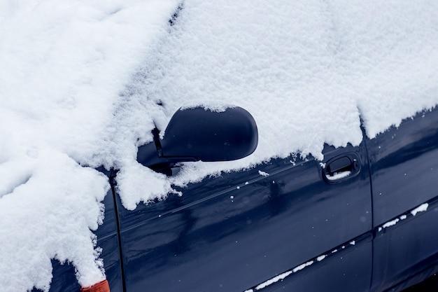 降雪後の雪に覆われた車。冬の悪化する気象条件
