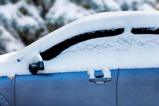 吹雪の中、雪に覆われた車。冬の厳しい気象条件_