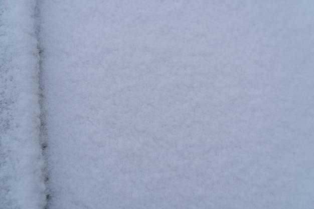 Заснеженный автомобиль, тающий снег на машине в теплое зимнее утро, концепция вождения в зимнее время с