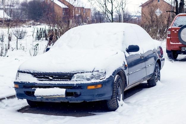 吹雪の後の冬の家の近くの雪に覆われた車。冬の悪天候