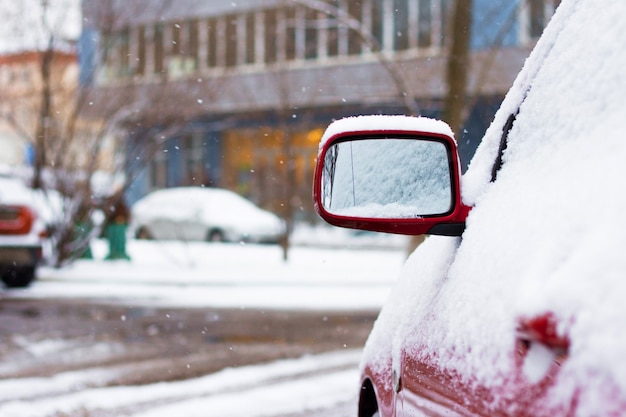 Snow-covered car on parking in winter. view of a side mirror machine
