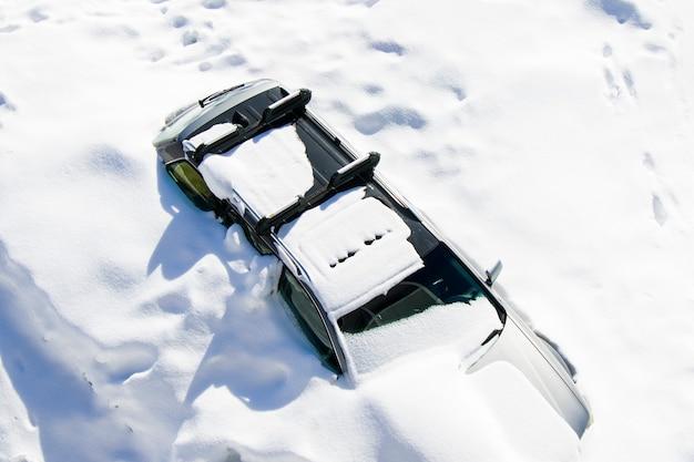 Заснеженный вид автомобиля, автомобиль в снегу. дневной и открытый.
