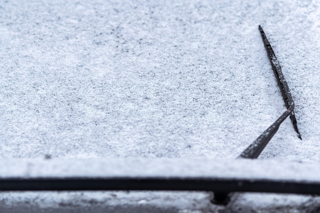 Snow covered car window with wipers