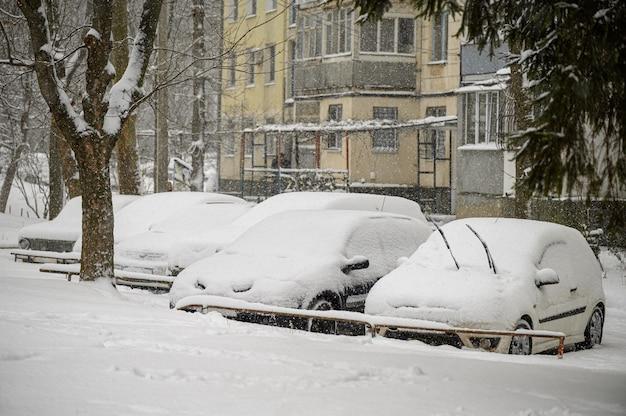 雪に覆われた車が駐車場で立ち往生