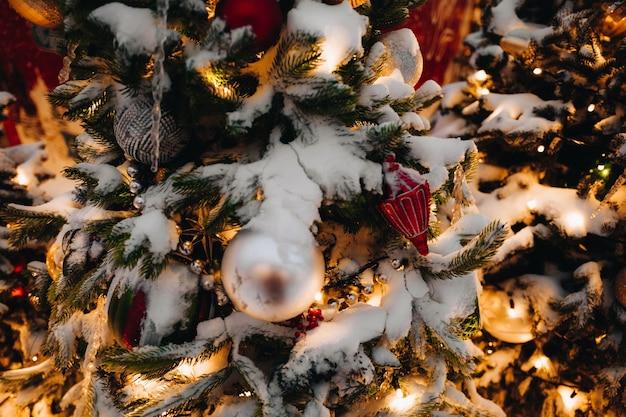 金色のお祝いボールのおもちゃとライトで飾られた雪に覆われたクリスマスツリーの枝新年