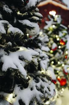 お祭りの背景におもちゃとボケライトで雪に覆われたクリスマスツリーメリークリスマス
