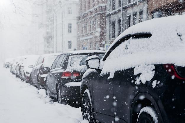 雪に覆われた街と車。豪雪。たくさんの雪。冬の天候の間に駐車場に駐車した車