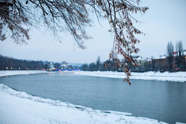 저녁 도시에서 눈 덮인 제방입니다. 아름다운 겨울 풍경