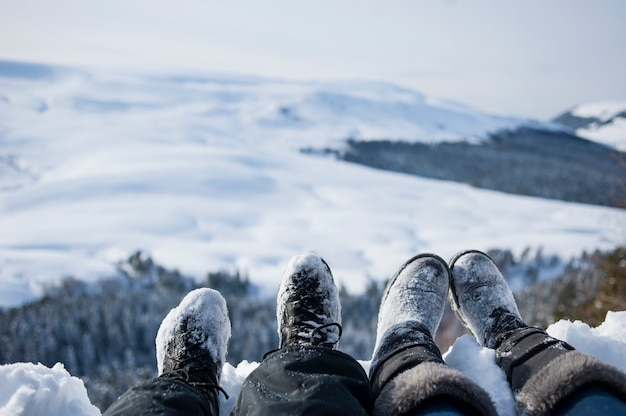 Snow-covered feet of two hikers on a winter landscape
