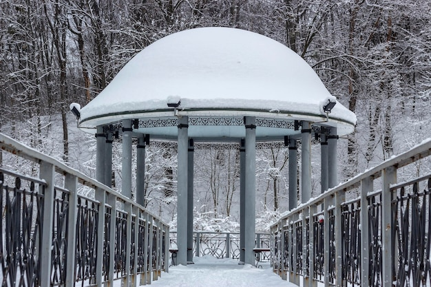 Snow-covered gazebo with a metal bridge in the middle of a lake in the park winter background