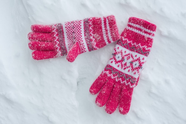 Snow covered gloves on snow, winter background.