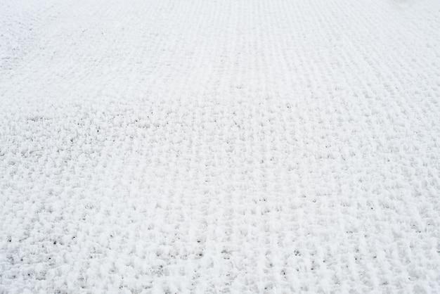 눈 덮인 그리드. 격자 울타리는 신선한 눈으로 덮여 있습니다. 겨울 배경 텍스처입니다.