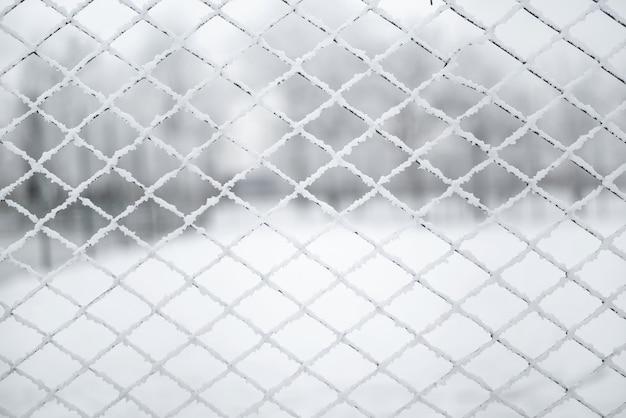 雪に覆われたグリッド。格子フェンスは新雪で覆われています。冬の背景のテクスチャ。