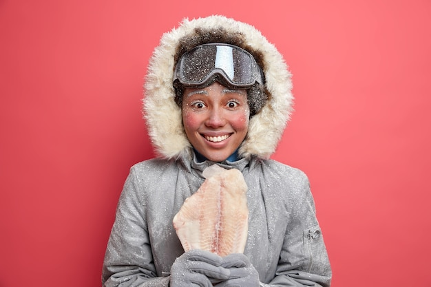 Snow covered happy arctic woman smiles broadly wears coat with hood and warm gloves holds frozen fish glad after going skiing fishing or snowboarding during winter time. active rest hobby concept