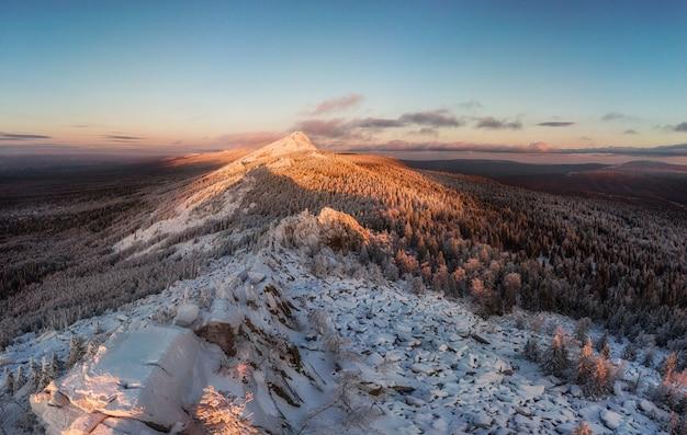 日没時の冬の雪に覆われた山脈。森と岩のトップビュー