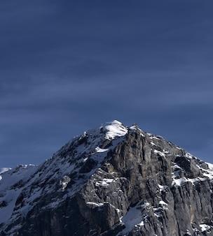 昼間は青空の下で雪に覆われた山
