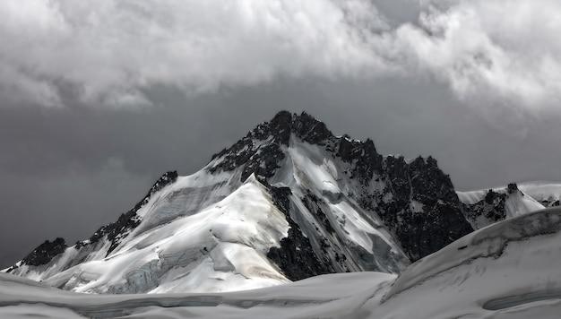 昼間は曇り空の下、雪に覆われた山