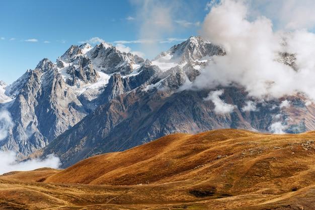 Заснеженные горы в тумане. осень у озера корульди