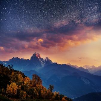 Заснеженные горы в тумане. осень на озере корулди
