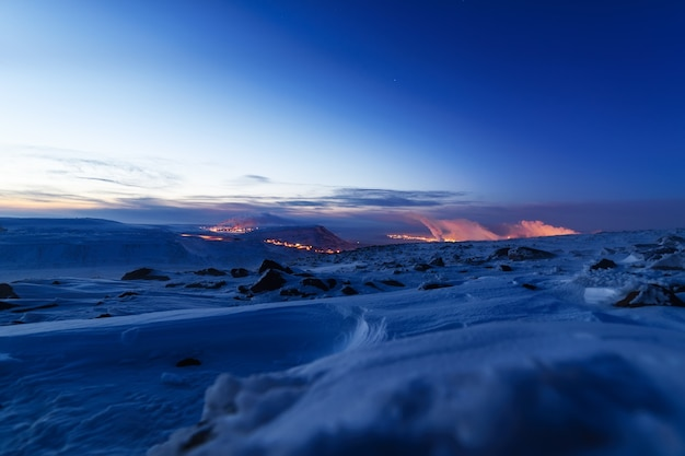 Snow-covered mountainside, night photo. in the distance the steel mills. russian far north .