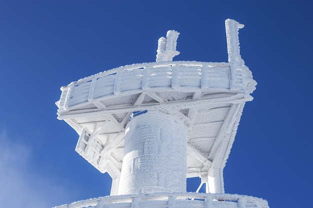 Snow-covered observation tower. heavy snow on the building