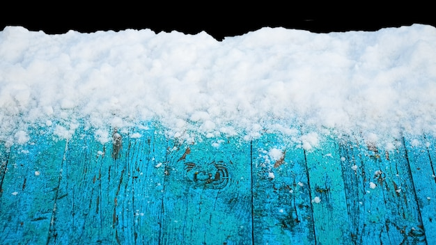 Snow-covered old blue boards on a black isolated background, winter background for design