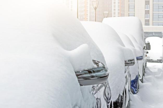 눈이 주차장에 차를 덮었습니다. 도시 현장, 눈보라.