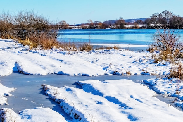 晴天時の雪に覆われた川岸
