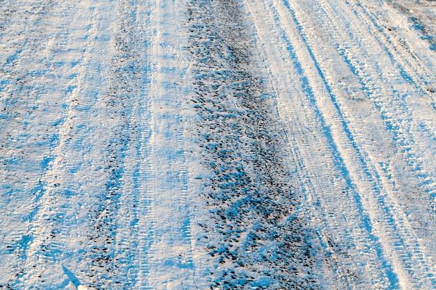最後の降雪後の雪に覆われた道路。線路と車輪をなぞる小道。