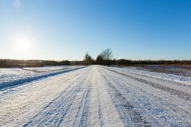 Заснеженная дорога, по которой остались следы проезда автомобиля. крупным планом, глубокие колеи на фоне голубого неба в солнечный день