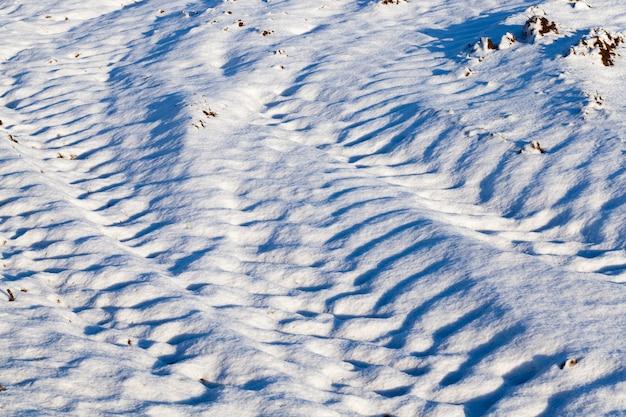 雪に覆われた道路で、運転する車の痕跡がありました。写真のクローズアップ、深いわだち掘れ