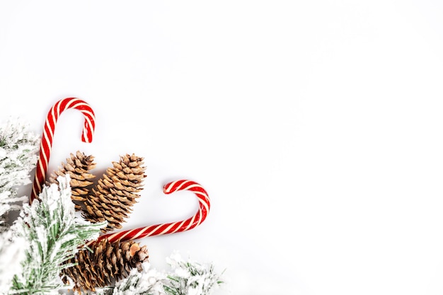Snow-covered spruce decorative branch with cones and christmas sweets on a white wall. space for text.