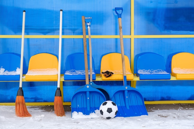 Snow-covered substitute bench and tools for clearing snow