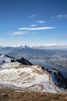 푸른 하늘 아래 리기 산과 스위스 호수의 탁 트인 전망이있는 눈 덮인 전망 데크
