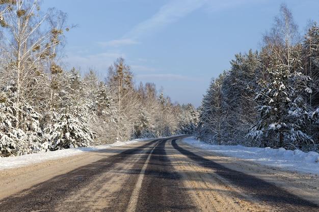 자동차 교통, 서리가 내린 눈 날씨 및 푸른 하늘을위한 눈 덮인 겨울 도로